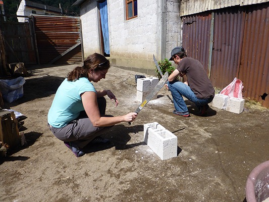 Sarah and Dave chopping cement blocks with machetes. It's amazing what you can do with a machete.