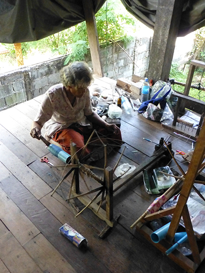 One of the weavers putting silk onto a bobbin.