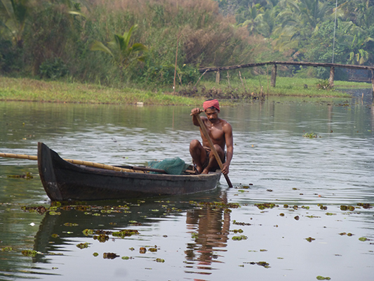 Local fisherman paddling to deeper waters.