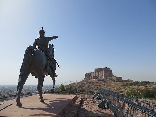 Statue of a man and horse near the Jaswant Thada mausoleum pointing to the Mehrangarh Fort.