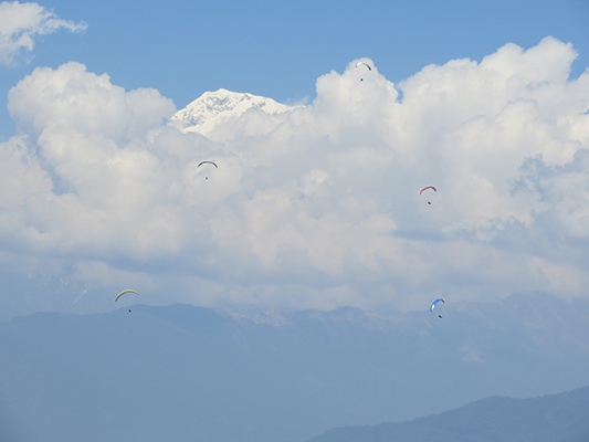 Clouded peak with paragliders